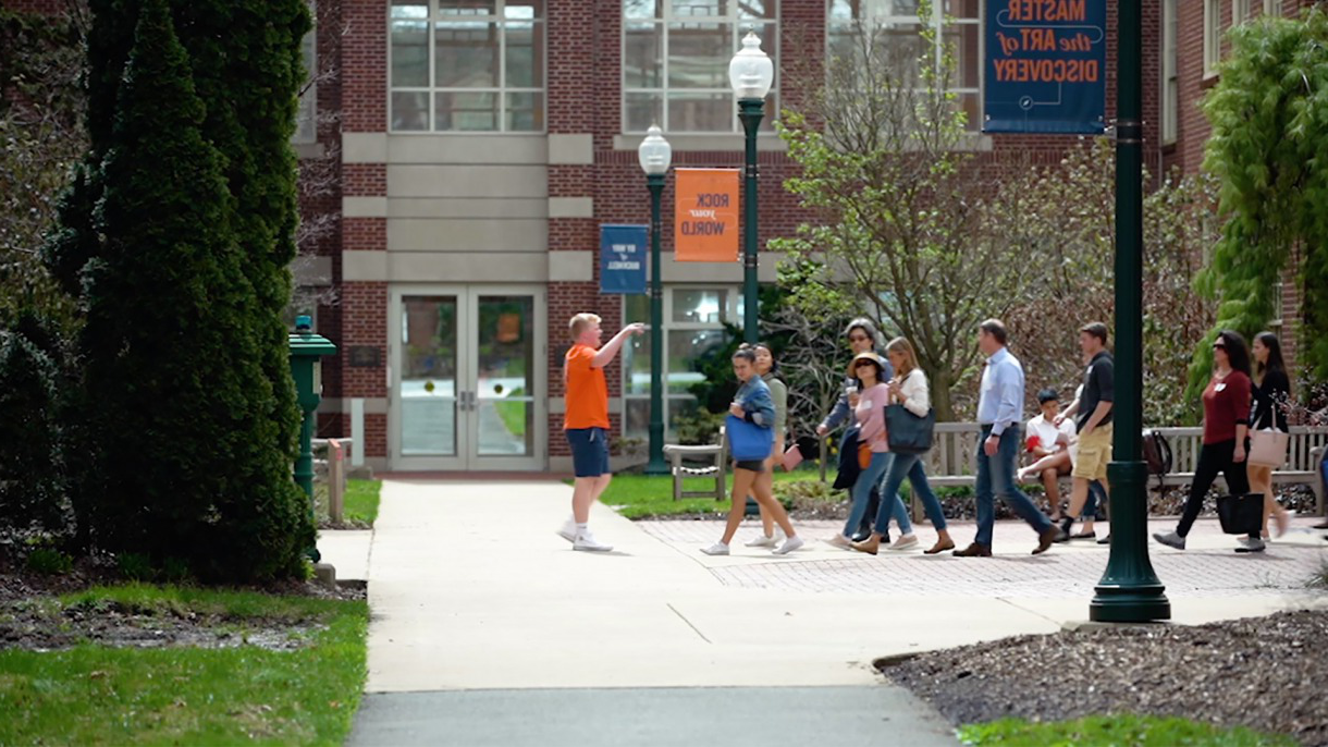 Students standing on sidewalk outside.