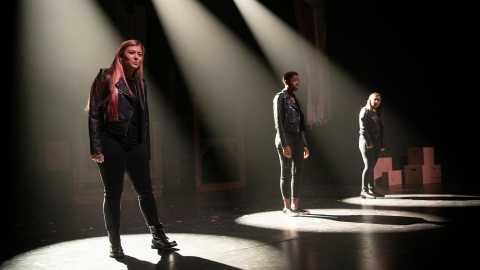 Three actresses stand on stage under spotlights.