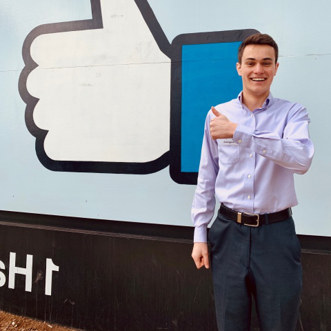 Ryan Bailis in front of Facebook的 sign.