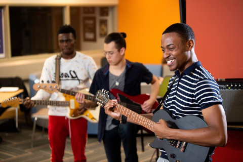 Three students playing their guitars